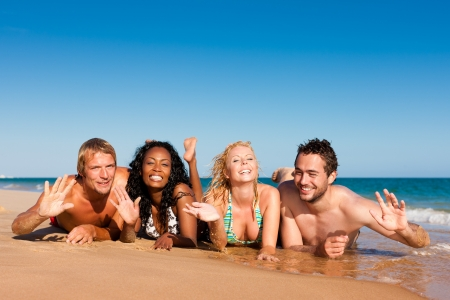 Group of Four friends - men and women - on the beach having lots of fun in their vacation   Stock Photo