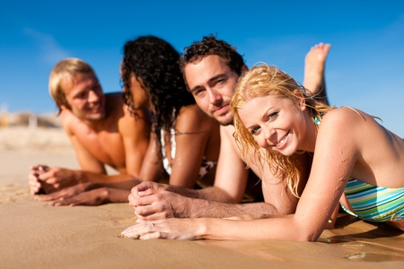 four friends: Group of Four friends - men and women - on the beach having lots of fun in their vacation   Stock Photo