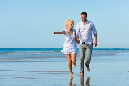 freedom couple: Couple on the beach in white clothing running down, they might be on vacation or even honeymoon