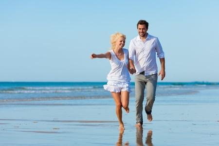 hombres corriendo: Pareja en la playa de ropa blanca en ejecuci�n, que sean de vacaciones o incluso Luna de miel Foto de archivo