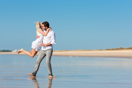 beachwear: Couple on the beach in white clothing running down, they might be on vacation or even honeymoon