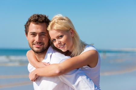 carrying girlfriend: Couple in love - Caucasian man having his woman piggyback on his back under a blue sky on a beach