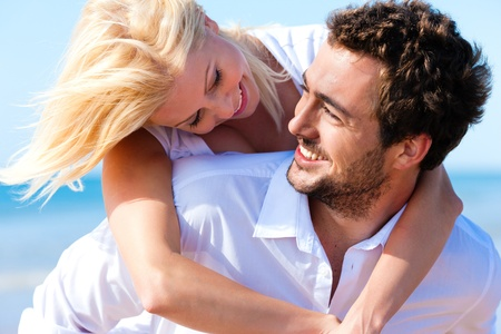 young couple smiling: Couple in love - Caucasian man having his woman piggyback on his back under a blue sky on a beach