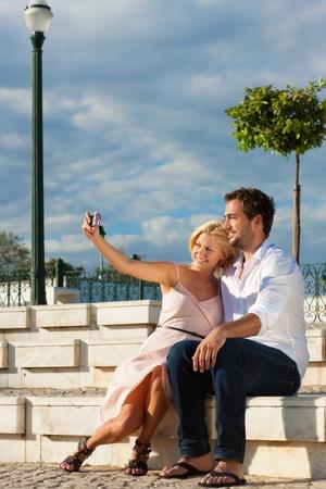 luna de miel: Pareja teniendo una ciudad rompe en verano sentado en un muro de ladrillo en la luz del sol, haciendo fotos   Foto de archivo
