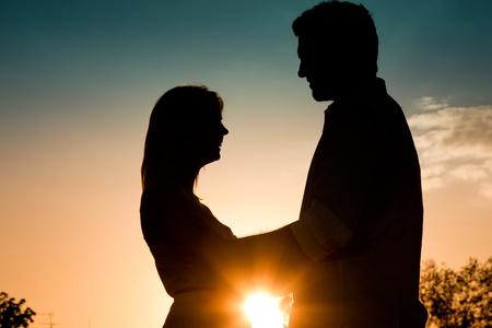 femme romantique: Couple dans l'amour de toucher l'autre r�tro-�clair� dans un coucher de soleil en �t�