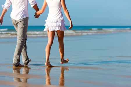 parejas caminando: Pareja en la playa de ropa blanca que ejecuta, que podrían ser de vacaciones o incluso Luna de miel