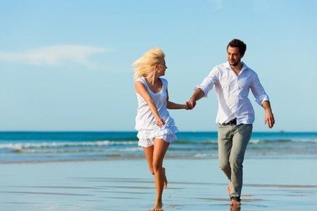 Couple on the beach in white clothing running down, they might be on vacation or even honeymoon photo
