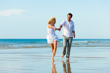 luna de miel: Pareja en la playa de ropa blanca en ejecuci�n, que sean de vacaciones o incluso Luna de miel Foto de archivo