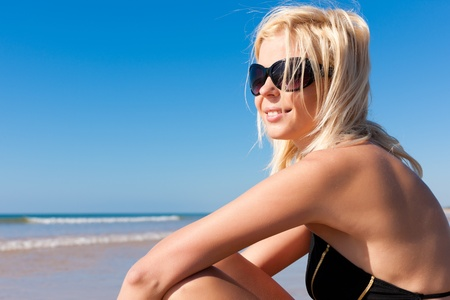 monokini: Attractive Woman in monokini sitting in the sun on beach, a lot of copyspace in the blue sky   Stock Photo