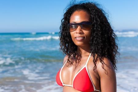 beachwear: Attractive Woman in bikini standing in the sun on beach with sun glasses