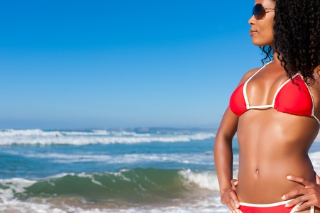 Attractive Woman in bikini standing in the sun on beach with sun glasses