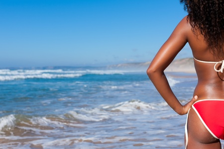 Attractive Woman in bikini standing in the sun on beach and looking into the water photo