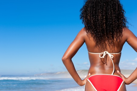 Attractive Woman in bikini standing in the sun on beach and looking into the water