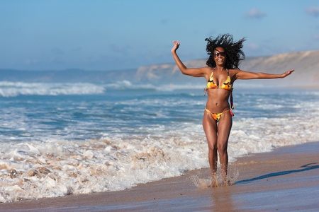 african bikini: Attractive Woman in bikini standing in the sun on beach, only part of looking over the sea, a lot of copyspace in the blue sky