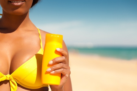 Woman in yellow bikini offering suncream on the beach in order to avoid sunburn, lots of copyspace   Stock Photo