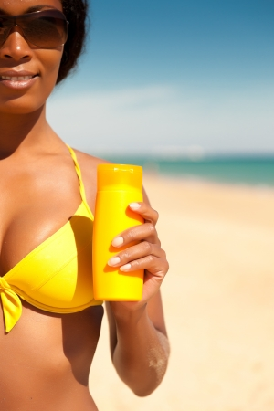 Frau im gelben Bikini Angebot Sonnencreme am Strand, um Sonnenbrand zu vermeiden, viel copyspace