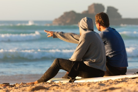 Two surfers sitting on their surf boards on the beach discussing the waves photo