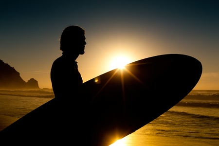surfer: Young surfer on the beach with his surf board over the head, looking at the ocean Stock Photo