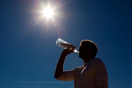 sediento: Hombre deportivo de agua potable de una botella contra un cielo azul de fondo bajo un sol caliente