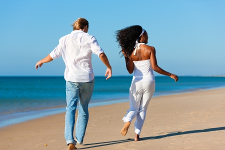 Happy couple - black woman and Caucasian man - walking and running down a beach in their vacation photo