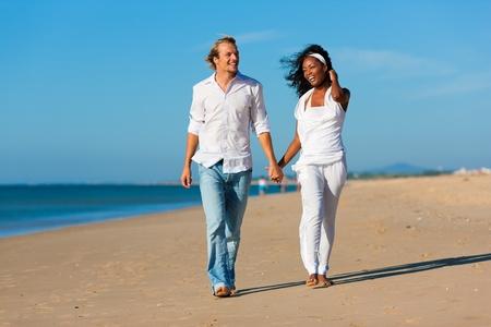 parejas caminando: Pareja feliz - mujer negra y hombre caucásico - caminando y corriendo por una playa en sus vacaciones