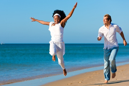 hombres corriendo: Feliz pareja - mujer negro y el C�ucaso - en la playa en sus vacaciones Foto de archivo