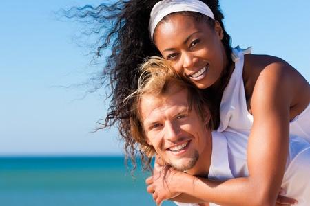 parejas caminando: Pareja feliz - mujer negra y hombre cauc�sico - en la playa en sus vacaciones