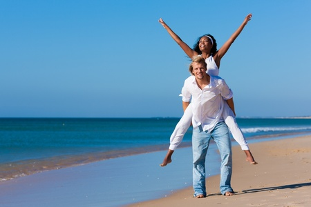 Gl�ckliches Paar - schwarze Frau und kaukasischen Mann - am Strand in ihrem Urlaub Lizenzfreie Bilder