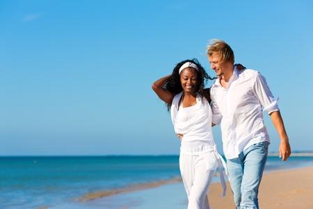 is playful: Pareja feliz - mujer negra y hombre caucásico - en la playa en sus vacaciones
