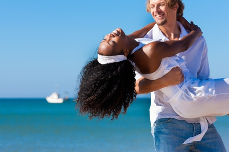 Happy couple - black woman and Caucasian man - at the beach in their vacation