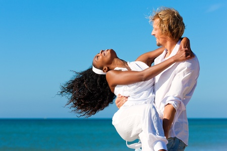 carrying girlfriend: Happy couple - black woman and Caucasian man - at the beach in their vacation