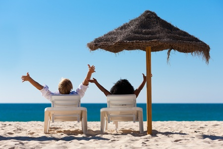 Couple sitting in sun chairs under an parasol sunshade on a beach stretching arms, feeling free Stok Fotoğraf