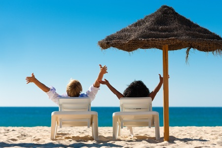 Couple sitting in sun chairs under an parasol sunshade on a beach stretching arms, feeling free Stock Photo