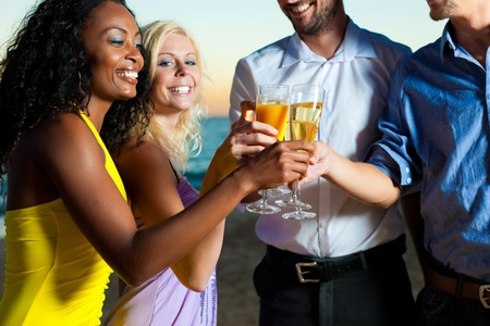 two couples: People (two couples) on the beach having a party, drinking and having a lot of fun in the sunset, they are wearing smart casual clothes and drink champagne