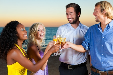 People (two couples) on the beach having a party, drinking and having a lot of fun in the sunset, they are wearing smart casual clothes and drink champagne Stock Photo - 10020841