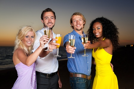 People (two couples) on the beach having a party, drinking and having a lot of fun in the sunset, they are wearing smart casual clothes and drink champagne Stock Photo - 10020527