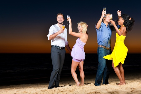 People (two couples) on the beach having a party, drinking and having a lot of fun in the sunset, they are wearing smart casual clothes and drink champagne photo