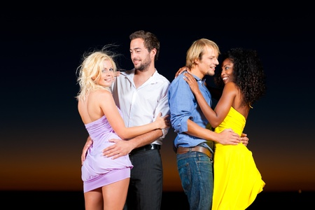 People (two couples) on the beach having a party and lots of fun in the sunset, they are wearing smart casual clothes and dance photo