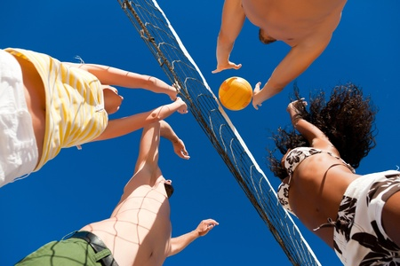 ballgame: Players doing summer sports trying to block a dangerous attack in a beach volleyball game