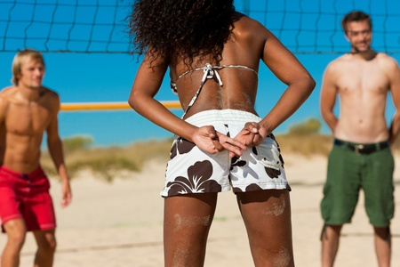 Friends playing beach volleyball, one girl giving the strategy to the player in the same team photo