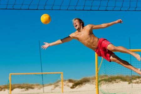 balon de voley: Hombre jugar voleibol de playa buceo después la pelota bajo un cielo azul claro