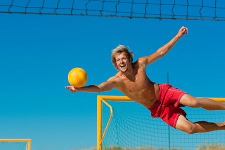 sky diving: Man playing beach volleyball diving after the ball under a clear blue sky