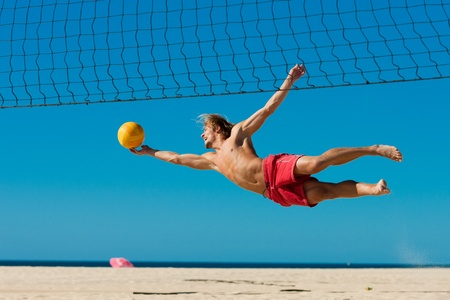 beach volleyball: Man playing beach volleyball diving after the ball under a clear blue sky
