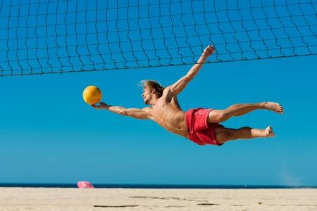 Man spielt Beachvolleyball Tauchen, nachdem der Ball unter einem klaren blauen Himmel