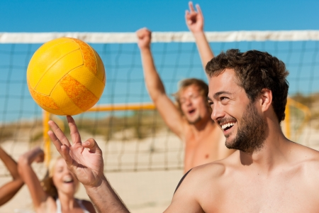 lazer: Group of friends - women and men - playing beach volleyball, one in front doing tricks to the ball