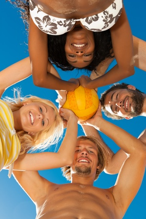 ballgame: Group of friends - women and men - playing beach volleyball, conceptional shot with all of them looking down with the ball at the camera  Stock Photo