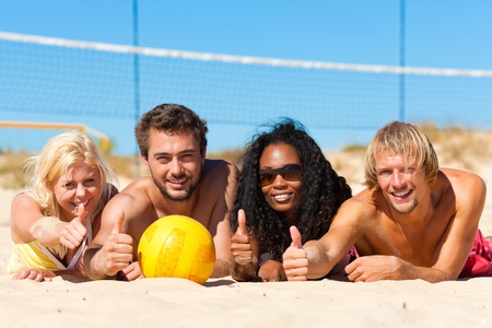 beach volleyball: Group of friends - women and men - playing beach volleyball; they having a break and lying in the sun Stock Photo