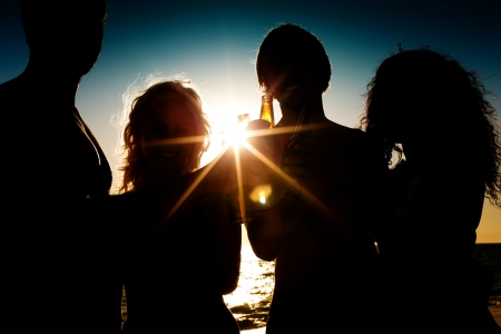 friends drinking: People (two couples) on the beach having a party, drinking and having a lot of fun in the sunset (only silhouette of people to be seen, people having bottles in their hands with the sun shining through)