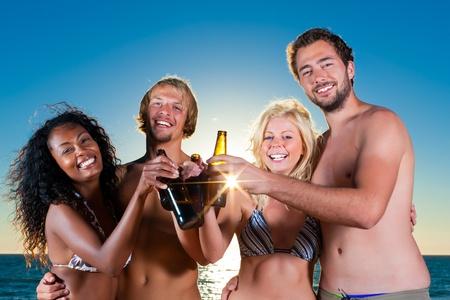 fiesta amigos: Grupo de cuatro amigos - hombres y mujeres - de pie con bebidas en la playa contra la puesta del sol sobre el Oc�ano