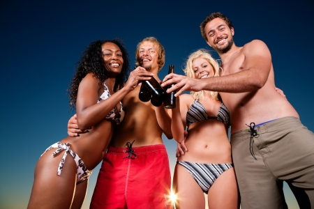 Group of four friends - men and women - standing with drinks on the beach against the setting sun over the ocean Stock Photo - 10020823